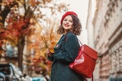 Outdoor autumn portrait of young fashionable happy smiling curly girl wearing gray coat, beret, with red leather backpack, posing in street of European city. Copy, empty space for text
