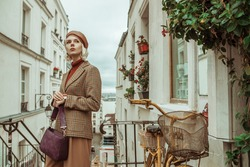 Outdoor autumn portrait of young  fashionable woman wearing trendy brown leather beret, turtleneck, beige houndstooth checkered blazer, holding purple bag, posing in street of Paris. Copy space