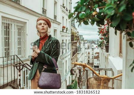 Outdoor autumn portrait of young  fashionable woman wearing trendy brown leather beret, turtleneck, green velour blazer, holding textured purple bag, posing in street of Paris. Copy space  Сток-фото ©