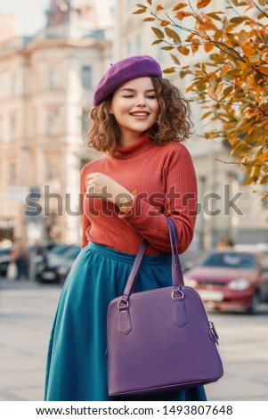 Outdoor autumn portrait of young happy smiling curly lady wearing elegant wrist watch, purple beret, orange turtleneck, blue skirt, holding faux leather handbag, posing in street of European city