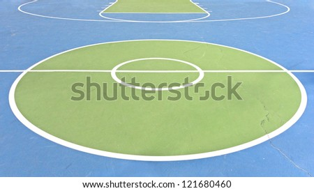 Outdoor basketball court. White lines and circles mark the various sections of a basketball court. A long crack in the painted concrete runs through the court. Horizontal view.