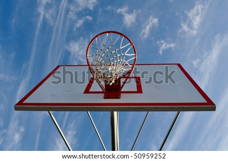 Outdoor Basketball Hoop Close Up with Clouds and Blue Sky