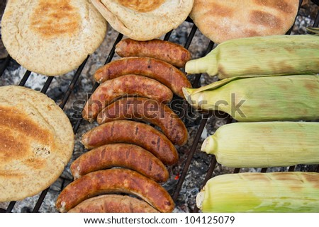 Outdoor BBQ with smokies, bread and corn, roasting.