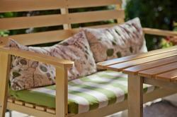 Outdoor bench furniture in a sunny summer garden.