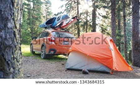 Outdoor Campsite with Tent and Sporty Orange Crossover Car with Kayaks on Roof Rack and Sunburst through Trees #1343684315