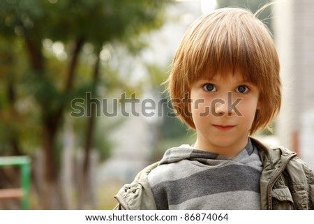 outdoor casual portrait of little cute blond caucasian boy five years old