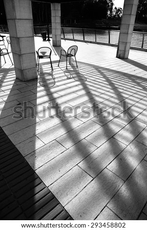Outdoor chairs with strong shadows natural effect. Counter light. Objects, light and shadows. Black and white.