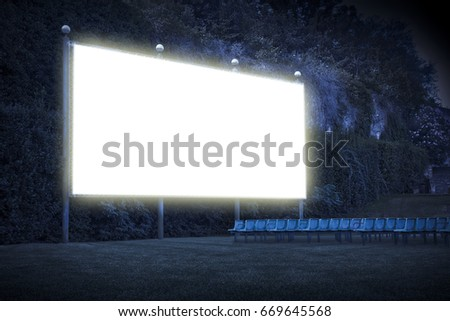 Outdoor cinema with chairs and white projection screen in nature - image with copy space