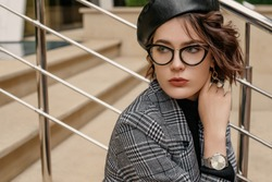 Outdoor close up fashion portrait of elegant confident woman, wearing stylish silver wrist, hand watch, glasses, black faux leather beret, checkered coat, posing on stairs. Copy, empty space for text