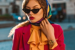 Outdoor close up fashion portrait of elegant woman wearing trendy colorful head scarf, black cat eye sunglasses, golden wrist watch, yellow blouse with jabot, pink blazer, walking in street of city