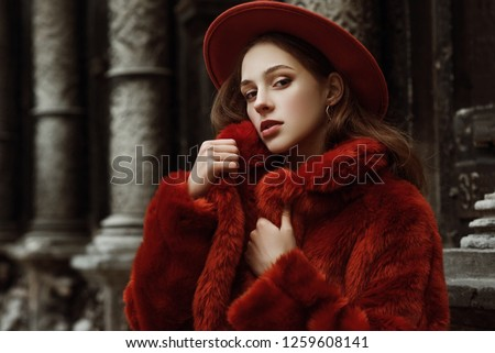 Outdoor close up fashion portrait of young beautiful confident woman wearing trendy orange faux fur coat, hat, silvery hoop earrings, posing in street of european city. Copy, empty space for text