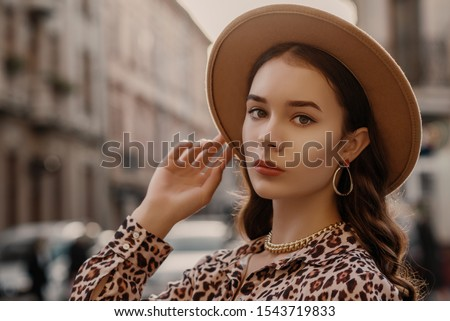 Outdoor close up fashion portrait of young elegant lady wearing beige fedora hat, trendy chain necklace, earrings, leopard print shirt, posing in street of European city. Copy, empty space for text Stock photo ©