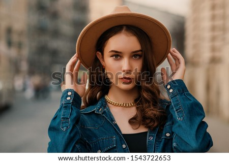 Outdoor close up fashion portrait of young elegant lady wearing beige fedora hat, trendy chain necklace, blue denim shirt, posing in street of European city. Copy, empty space for text Stock photo ©