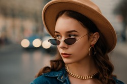 Outdoor close up fashion portrait of young elegant lady wearing beige hat, trendy sunglasses, earrings, chain necklace, denim shirt, posing in street of European city. Copy, empty space for text