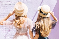Outdoor close-up portrait from back of fair-haired curly sisters spending time together in sunny morning. Two slim ladies in trendy romantic outfit looking at wall holding straw hats.