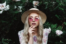 Outdoor close up portrait of beautiful young woman with long blonde hair, makeup, wearing pink cat eye sunglasses, straw boater hat posing in the blooming garden.  Female spring fashion concept