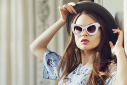 Outdoor close up portrait of young beautiful fashionable woman posing in street. Model wearing stylish gray boater hat, retro white sunglasses. Female fashion concept. Copy, empty space for text
