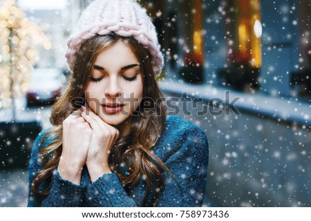 Outdoor close up portrait of young beautiful girl with long hair wearing hat, sweater posing in street of european city.  Christmas, winter holidays concept. Snowfall. Copy, empty space for text #758973436