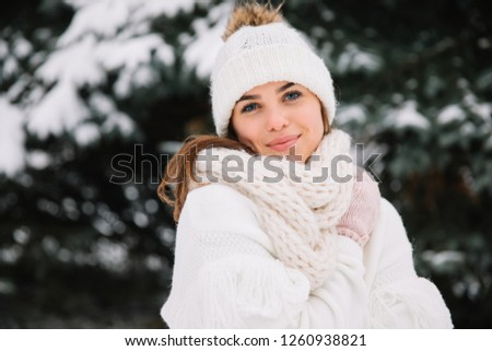 Outdoor close up portrait of young beautiful happy smiling girl wearing white knitted beanie hat, scarf and gloves. Model posing in park with Christmas lights. Winter holidays concept. #1260938821
