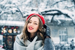Outdoor close up portrait of young beautiful happy smiling girl with red lips, wearing beret, posing in street of european city. Winter fashion, holidays concept