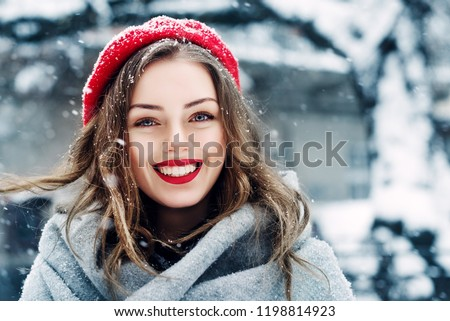 Outdoor close up portrait of young beautiful happy smiling girl with red lips, wearing french style beret, posing in street of european city. Winter fashion, Christmas holidays concept. Copy space