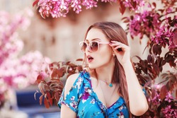 Outdoor close up portrait of young beautiful surprised girl looking aside, wearing stylish pink sunglasses, earrings, necklace,  posing in street, near spring blooming tree. Female fashion. Copy space