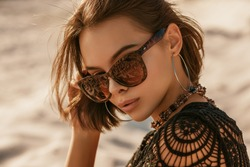 Outdoor close up portrait of young beautiful woman with tanned skin wearing luxury wide frame square sunglasses, hoop earrings, crochet top, posing on sand, at sunset. Copy, empty space for text