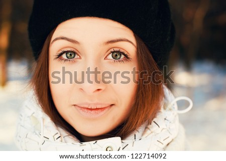 Outdoor closeup portrait of a young beautiful girl in black cap