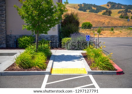 Outdoor Concret ramp way and yellow tactilel with disabled sign for support wheelchair disabled people.
