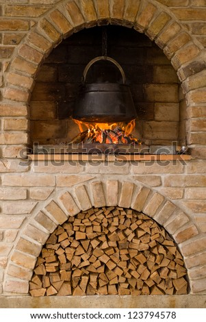 Outdoor cooking in a barbecue fireplace, kettle of boiling fish stew