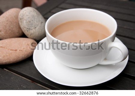 Outdoor cup of tea in a white cup and saucer with stones on a wooden background