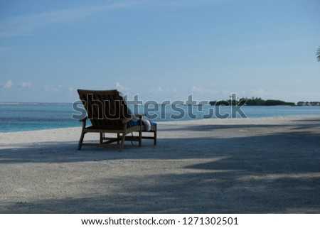 Outdoor deck chair in open air shadows on white sand beach in Maldive island resort, wide sunny blue sky and sea ocean horizon. comfortable relaxing sunbathe concept #1271302501