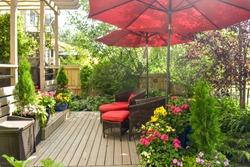 Outdoor deck in urban oasis garden in summer sunshine