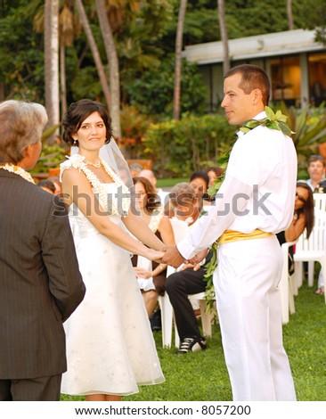 Outdoor destination wedding in Hawaii; happy couple holding hands