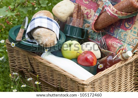 outdoor dining : picnic basket on lawn with fresh olive-baguette, milk, apple and sausages, bread and pieplant juice.