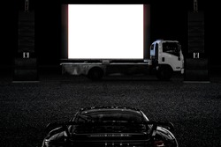 Outdoor drive in theater audience in luxury saloon and with mobile truck cinema in light night as activity during social distancing adapt to new normal of the coronavirus COVID-19 pandemic