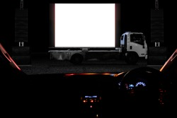 Outdoor drive in theater or drive in cinema, with mobile truck cinema in light night as activity during social distancing adapt to new normal of the coronavirus COVID-19 pandemic.