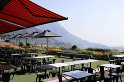 Outdoor exterior table and chair place  outside of restaurant and coffee cafe with beautiful  mountain viewpoint and morning sunlight in the background. - image