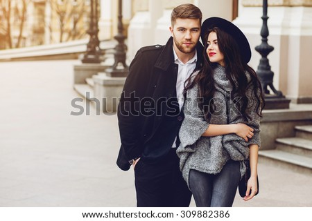 Outdoor fall portrait of fashionable pretty young couple wearing trendy  outfit . Two lovers posing against theater background in autumn sunlight.