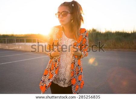Outdoor fashion and lifestyle portrait of trendy woman posing at sunset in trendy jacket and summer bright outfit,enjoy her summer holidays,vacation outfit,summer look,trendy girl,accessories,urban