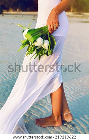 Outdoor fashion image of bride posing alone at exotic beach at sunset with beautiful wedding lotus bouquet, have nice simple trendy white dress.