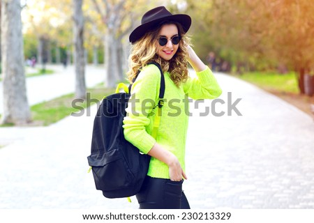 Outdoor fashion image of stylish hipster girl wearing neon sweater sunglasses and vintage hat, walking with back pack on the street in nice sunny fall autumn day. #230213329