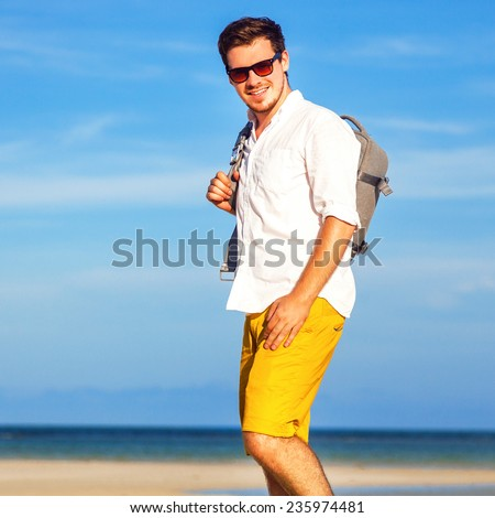 Outdoor fashion lifestyle image of young traveler handsome hipster man, wearing bright yellow shorts sunglasses, and holding his backpack, ready for adventures. Amazing view on beach and blue sky.