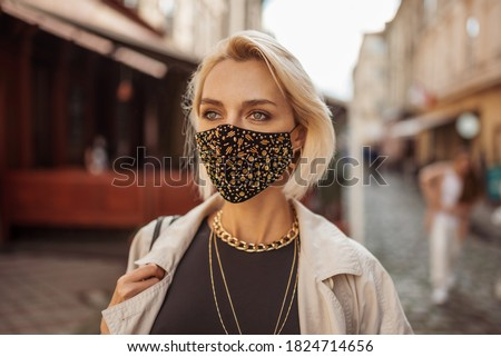 Outdoor fashion, lifestyle portrait of elegant woman wearing trendy outfit with protective face mask, many golden chain necklaces, walking in street of European city. Copy, empty space for text