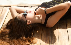 Outdoor fashion look of young woman wearing summer sunglasses,laying and laughing on the beach of sand,having sunbath.Wear summer bright outfit,vintage summer outfit colors.Hipster teenager girl