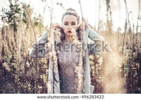 Outdoor fashion photo of young beautiful lady in autumn landscape with dry flowers.\ Autumn/Winter. Warm autumn/winter. Fashion autumn/winter. Beautiful autumn. Sunny autumn, Cozy autumn coat