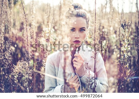 Outdoor fashion photo of young beautiful lady in autumn landscape with dry flowers. Autumn/Winter. Warm autumn/winter. Fashion autumn/winter. Beautiful autumn. Sunny autumn, Cozy autumn sweater