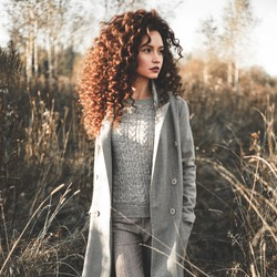 Outdoor fashion photo of young beautiful lady in autumn landscape with dry flowers. Gray coat, knitted sweater, wine lipstick. Fashion lookbook. Warm Autumn. Warm Spring