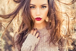 Outdoor fashion photo of young beautiful lady in autumn landscape with dry flowers. Knitted sweater, wine lipstick. Warm Autumn. Warm Spring