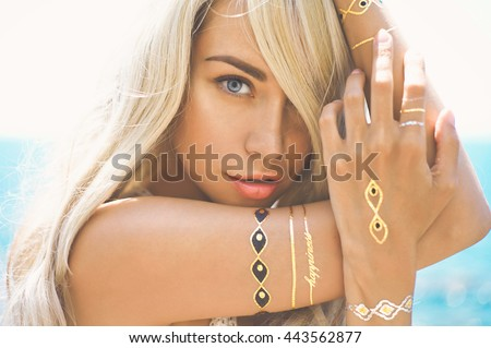 Outdoor fashion portrait of beautiful blonde lady at beach with flash tattoo